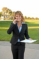 Business woman using mobile phone in park