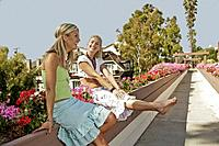 Two women relaxing together and laughing on walkway