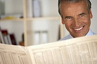 Smiling senior businessman reading a newspaper