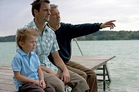Boy, father and grandfather sitting on a wooden footbridge at a lake