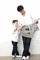 Father reading newspaper and son using mobile phone