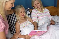 Mother sitting at the bed of her two blond daughters, all looking at a book for children, close_up