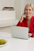 Blond woman sitting behind a laptop while phoning