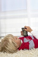 Boy 4_5 Years lying on floor using a handheld