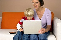 Mother and son 4_5 Years sitting on a sofa und using a laptop