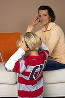 Mother phoning with a mobile phone on a sofa, son 4_5 Years listening to music about earphones
