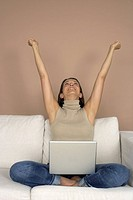 Woman sitting with a laptop on a sofa, rising arms up