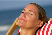 Young blond woman sunbathing on a beach chair, close_up