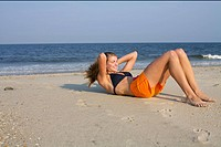Young woman doing sit_ups at the beach