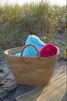 Basket with towels on a dune at the beach, close_up
