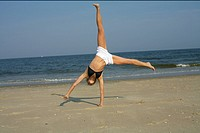 Young woman doing cartwheel, outdoors