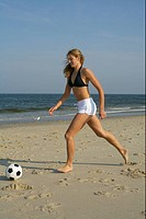 Young blond woman playing football at the beach