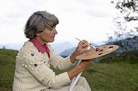 Senior adult woman sitting on a meadow while painting with a color palette, close_up