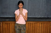 Indian woman with her hands folded in front of a blackboard