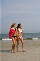 Two young women walking next to each other at the beach with a towel over their back