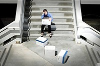 Businesswoman sitting on steps by dropped boxes of paperwork