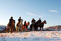 Wranglers leading their horses over the snowcaped ranges of wyoming at sunset