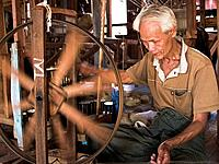 Man spinning lotus threads into silk at Inle Lake in Myanmar