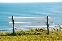 White wooden bench facing Wanui's beach landscape in Raglan, world famous surfing town in the Waikato region, New Zealand, North Island