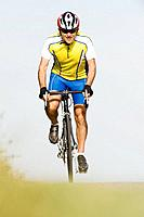 Cyclist riding bicycle, front view