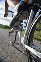 Close_up of a cyclist cycling on road