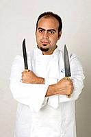 Young latin Chef holding two knives looking at the camera