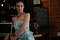 Portrait of young woman standing at bar in cafe.