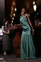 Young happy African_American woman in gown at bar.