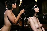 Young nude woman blindfolding woman at burlesque bar