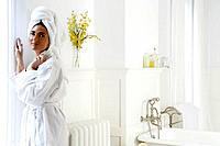 Woman standing in bathroom in bathrobe