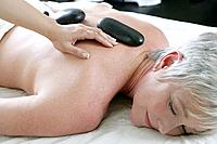 Mature woman getting hot stone massage