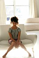 Young stylish woman sitting on couch