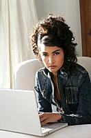 Young stylish woman using laptop