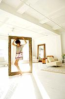 Young stylish woman standing in picture frame