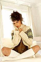 Portrait of young stylish woman sitting indoors (thumbnail)