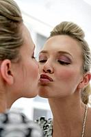 Young woman kissing mirror