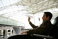 Young businessman throwing paper airplane in airport