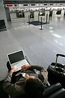 Young businessman using laptop in airport.