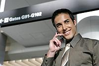 Young businessman on the phone in airport.