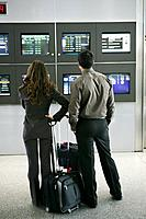 Businesspeople looking at departure screens at airport