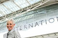 Mature woman standing in front of airport