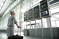 Mature woman looking at departure screens at airport
