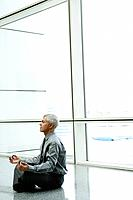 Mature businessman doing yoga in airport