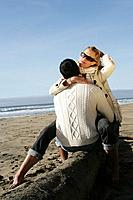 Young couple hugging at beach in winter