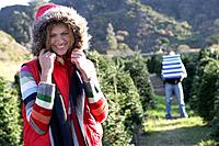 Young happy woman in Christmas tree field with man carrying gifts behind
