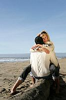Young couple hugging on beach in winter.