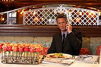 Portrait of business man at restaurant table, using mobile phone, newspaper and laptop by plate