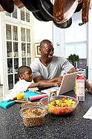 Father and son 6_7 using laptop at kitchen counter
