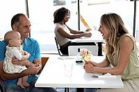 Man and woman sitting at table in cafe, man carrying baby 0_6 months, smiling