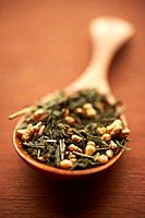 Dried genmaicha green tea in wooden spoon, close_up